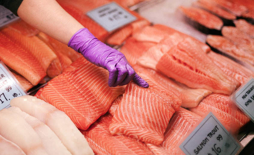 Rainbow trout meat in a fish store and a woman pointing to fish